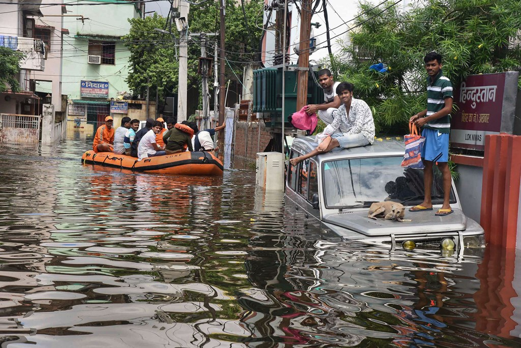 Patna: NDRF personnel rescue flood-affected residents as others sit atop an SUV following heavy monsoon rainfall, in Patna, Tuesday, Oct. 1, 2019. (PTI Photo) (PTI10_1_2019_000270B)