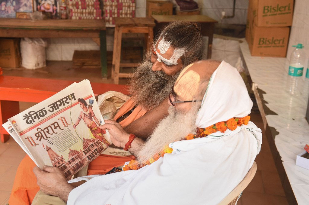 Ayodhya: Sadhus read newspaper fronted with headlines on Ayodhya case verdict, in Ayodhya, Sunday, Nov. 10, 2019. The Supreme Court in a historic verdict on Saturday, Nov. 9, 2019, backed the construction of a Ram temple by a trust at the disputed site in Ayodhya and ruled that an alternative five-acre plot must be found for a mosque in the Hindu holy town. (PTI Photo/Nand Kumar) -(PTI11_10_2019_000051B)