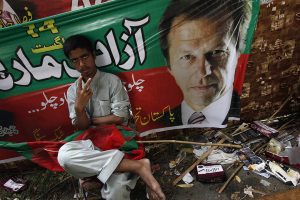 A supporter of Imran Khan, chairman of Pakistan Tehreek-e-Insaf (PTI) political party, gestures while sitting outside Khan's residence before the start of today's Freedom March in Lahore August 14, 2014. Thousands of protesters preparing to march on the Pakistani capital gathered in the eastern city of Lahore on Thursday, buoyed by a last-minute court order that a peaceful march could go ahead and a government promise to obey the ruling. REUTERS/Akhtar Soomro (PAKISTAN - Tags: POLITICS CIVIL UNREST CRIME LAW)