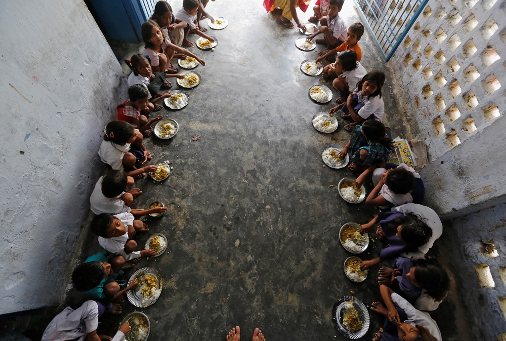 School children eat their free mid-day meal, distributed by a government-run primary school, at Brahimpur village in Chapra district of the eastern Indian state of Bihar July 19, 2013. Police suspect that India's worst outbreak of mass food poisoning in years was caused by cooking oil that had been kept in a container previously used to store pesticide, the magistrate overseeing the investigation said on Friday. REUTERS/Adnan Abidi