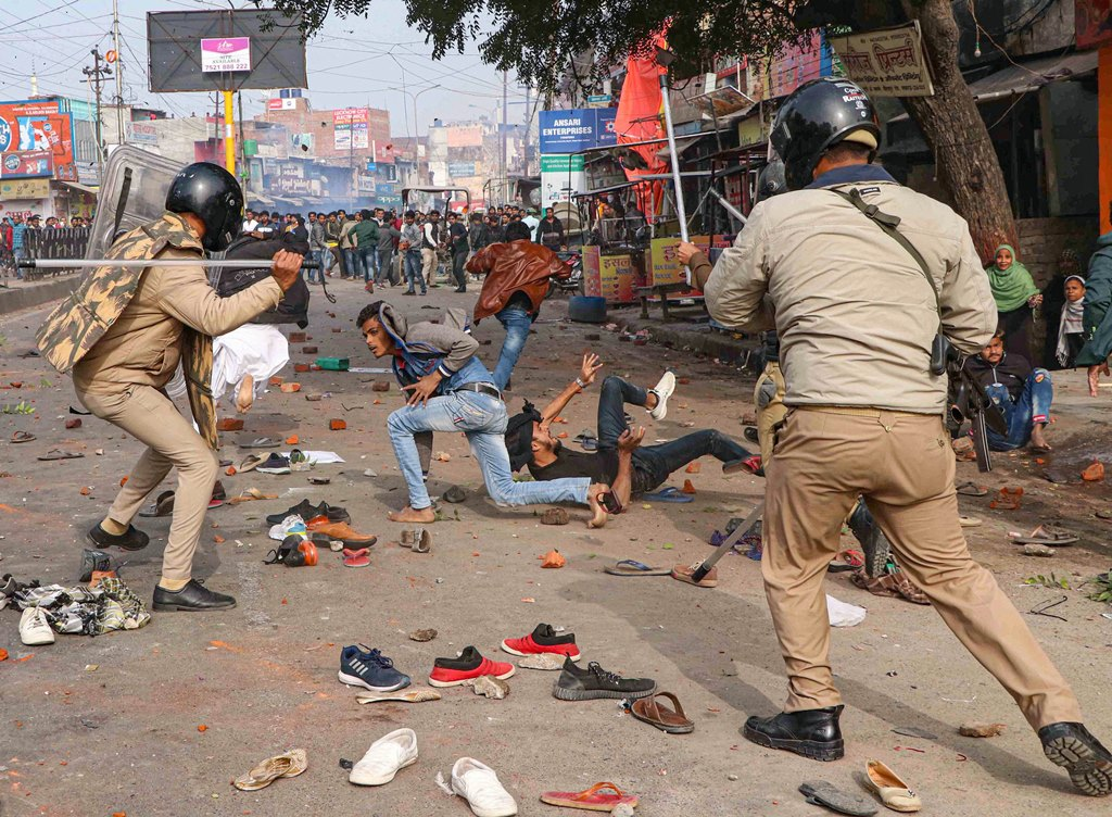 Lucknow: Police personnel baton charge at protestors during their rally against NRC and amended Citizenship Act that turned violent, in Lucknow, Thursday, Dec. 19, 2019. (PTI Photo) (PTI12_19_2019_000292B)