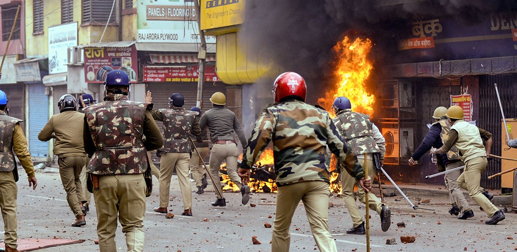 Muzaffarnagar: Police run past a burning bank building as they clash with protestors during a rally against the Citizenship (Amendment) Act, in Muzaffarnagar, Friday, Dec. 20, 2019. (PTI Photo)(PTI12_20_2019_000239B)