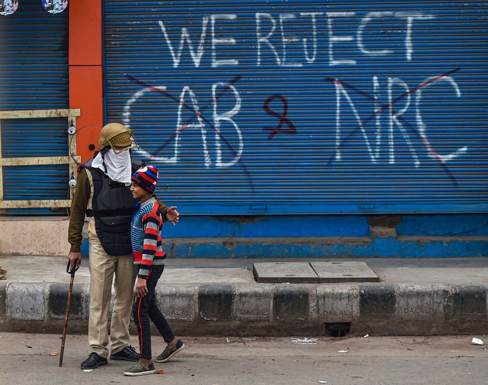 New Delhi: A policeman interacts with a boy while guarding during a protest demonstration demanding withdrawal of Citizenship Amendment Act (CAA), at Seelampur in New Delhi, Tuesday, Dec. 17, 2019. (PTI Photo/Manvender Vashist) (PTI12_17_2019_000259B)