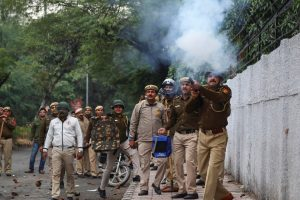 New Delhi: A police personnel fires tear gas as students ofJamiaMillia Islamia University stage aprotest against the passing of Citizenship Amendment Bill, in New Delhi, Friday, Dec. 13, 2019. (PTI Photo) (PTI12_13_2019_000384B)