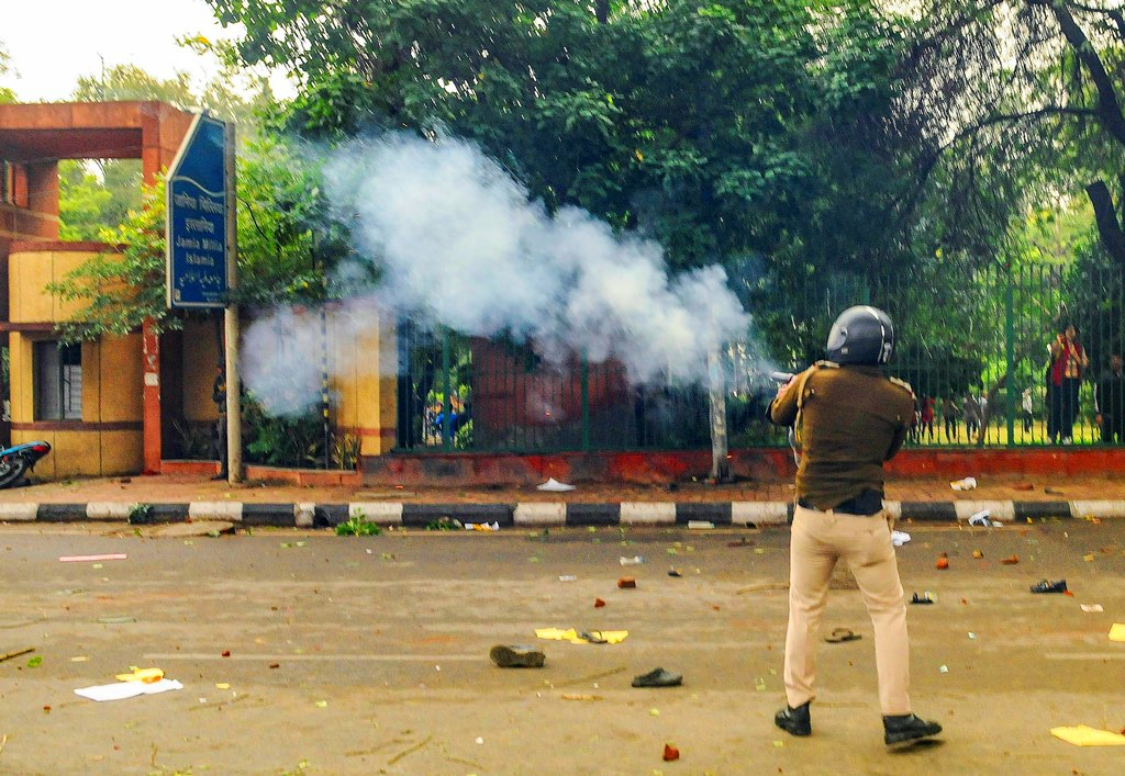 New Delhi: A police personnel fires tear gas as students of Jamia Millia Islamia University stage a protest against the passing of Citizenship Amendment Bill, in New Delhi, Friday, Dec. 13, 2019. (PTI Photo) (PTI12_13_2019_000371B)