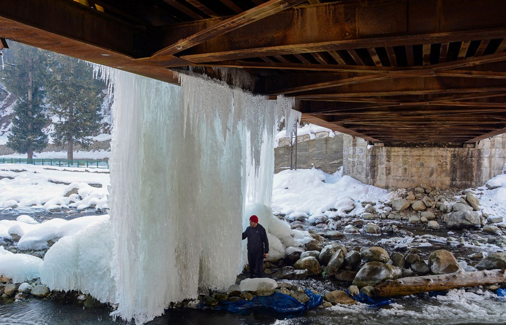 Srinagar: A man looks at icicles hanging from a bridge after snowfall at Tangmarg near Srinagar, Monday, Dec. 30, 2019. (PTI Photo) (PTI12_30_2019_000134B)
