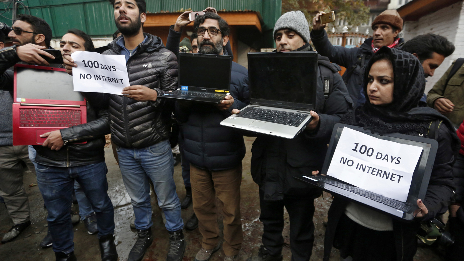 Kashmiri journalists display laptops and placards during a protest demanding restoration of internet service, in Srinagar, November 12, 2019. REUTERS/Danish Ismail - RC2O9D9L2D29