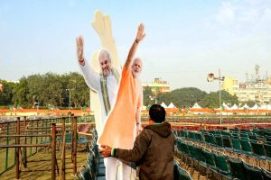 New Delhi: A workers carries cut-outs of Prime Minister Narendra Modi and Union Home Minister Amit Shah on the eve of  BJP rally at Ramlila Maidan in New Delhi, Saturday, Dec. 21, 2019. (PTI Photo)(PTI12_21_2019_000185B)