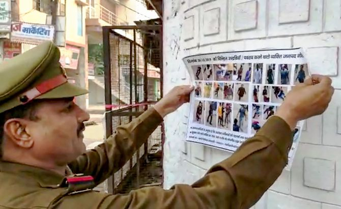 Gorakhpur: A police personnel sticks a collage of people involved in violence during protest on Friday after Juma Namaz against CAA and NRC, obtained from video footage and CCTV camera footage, in Gorakhpur, Saturday, Dec. 21, 2019. (PTI Photo) (PTI12_21_2019_000219B)