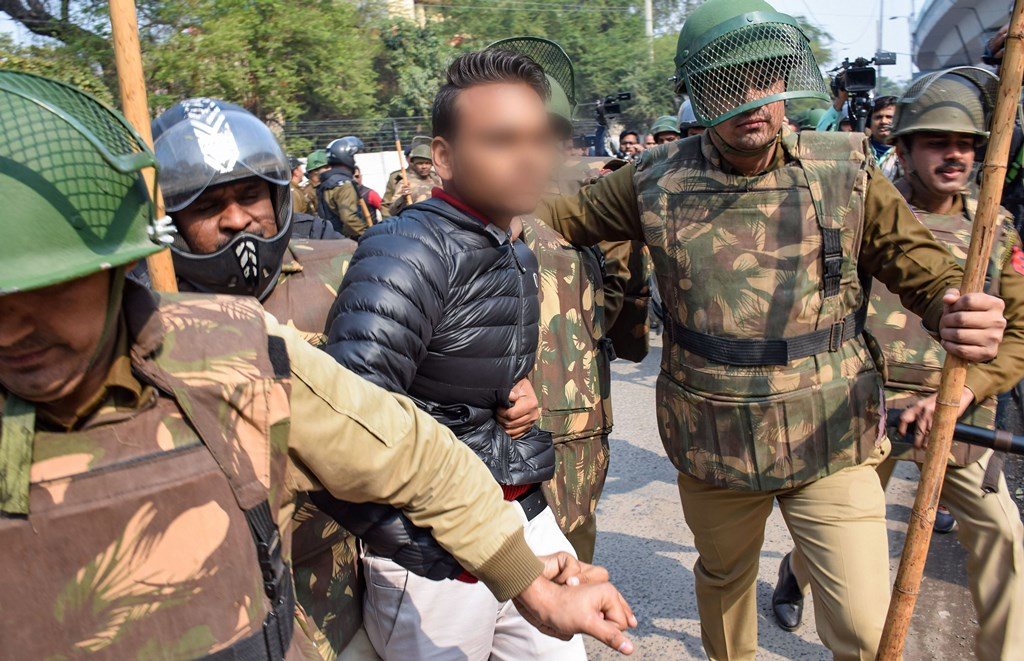 New Delhi: Police detain an unidentified person (face blurred as his being an adult could not be ascertained), after he allegedly brandished a gun and opened fire towards students protesting against the Citizenship Amendment Act, near Jamia Millia Islamia University, in New Delhi, Thursday, Jan. 30, 2020. (PTI Photo) (PTI1_30_2020_000178B) *** Local Caption ***