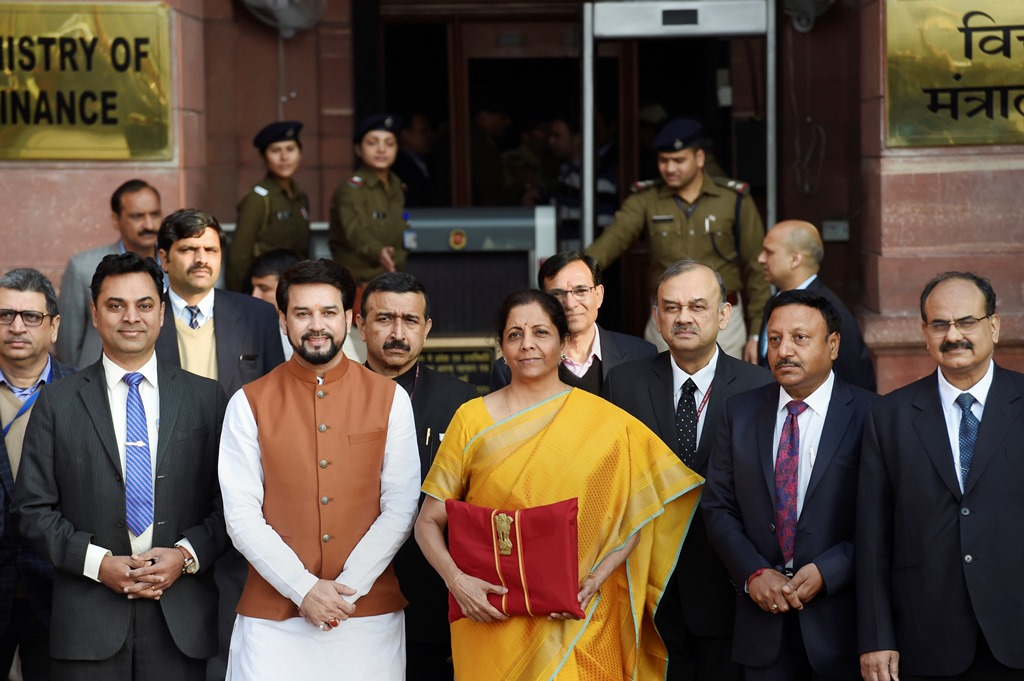 New Delhi: Union Finance Minister Nirmala Sitharaman, holding a folder containing the Union Budget documents, poses for photographers along with her deputy Anurag Thakur and a team of officials, outside the Ministry of Finance, North Block in New Delhi, Saturday, Feb. 1, 2020. (PTI Photo/Kamal Singh) (PTI2_1_2020_000013B)