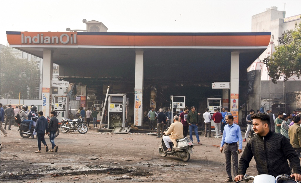 New Delhi: Passersby look at the charred petrol pump which was set ablaze by rioters yesterday during clashes over the new citizenship law, in Bhajanpura area of East Delhi, Tuesday, Feb. 25, 2020. (PTI Photo) (PTI2_25_2020_000072B)