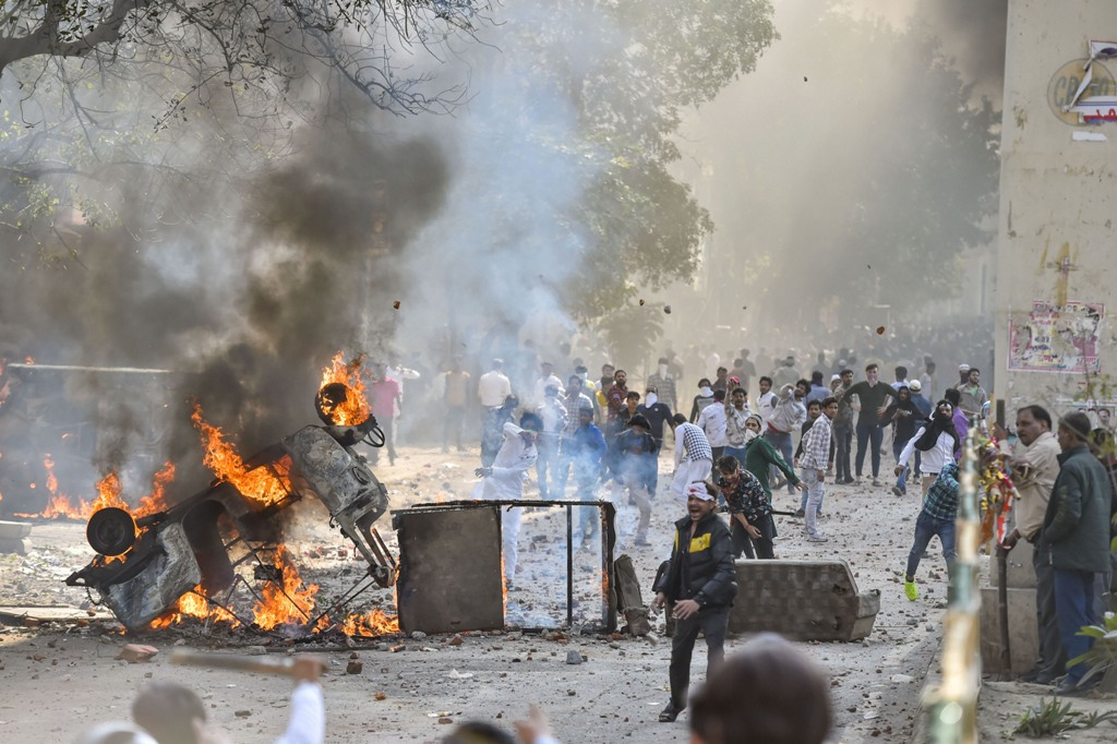 New Delhi: Vehicles set ablaze as protestors throw brick-bats during clashes between a group of anti-CAA protestors and supporters of the new citizenship act, at Jafrabad in north-east Delhi, Monday, Feb. 24, 2020. (PTI Photo/Ravi Choudhary)(PTI2_24_2020_000218B) *** Local Caption ***