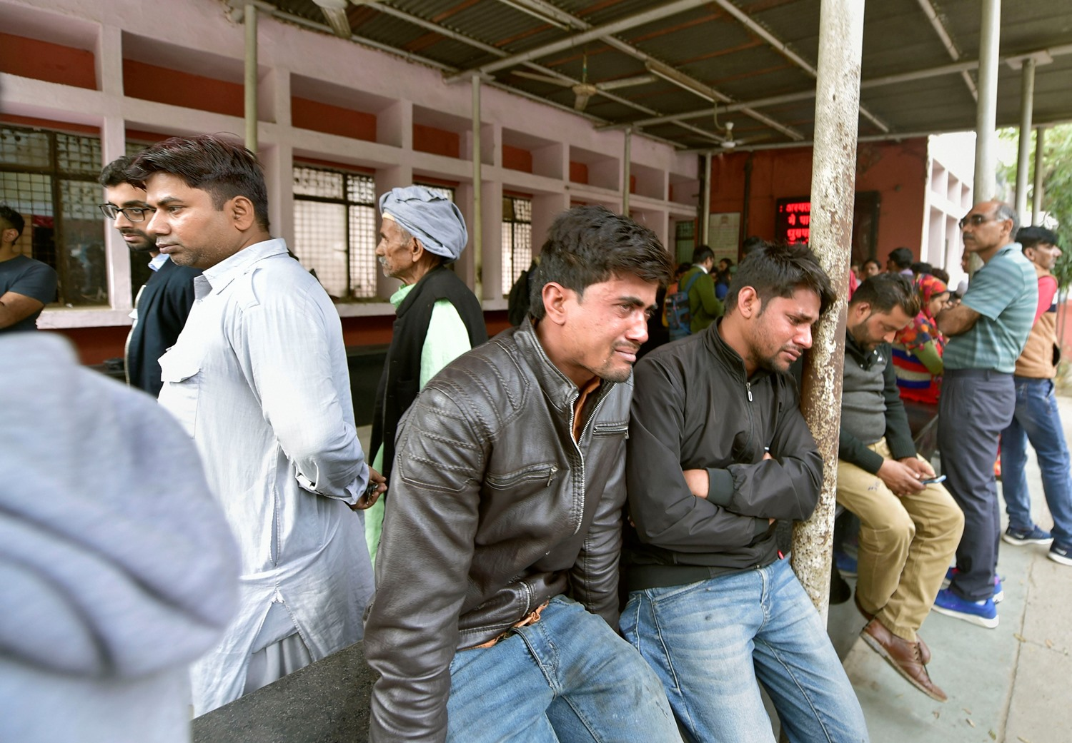 New Delhi: Shahzad (on right sitting next to a pole) weeps as he waits to receive the body of his friend Mohsin Ali, who was killed during communal violence in northeast Delhi area over the amended citizenship law, outside the mortuary of GTB hospital in New Delhi, Thursday, Feb 27, 2020. The death toll in the communal violence has reached 32 on Thursday. (PTI Photo/Vijay Verma)(PTI2_27_2020_000066B)