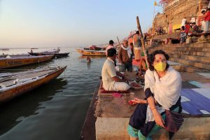 Varanasi: A woman wearing a protective mask sits near an near deserted bank of River Ganga in the wake of coronavirus pandemic, in Varanasi, Friday, March 20, 2020. (PTI Photo)(PTI20-03-2020_000035B)