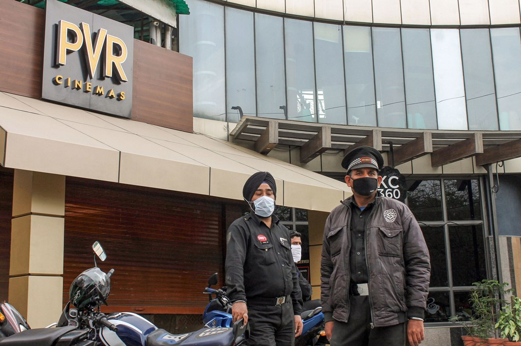 Jammu: Security personnel wear masks to mitigate the spread of coronavirus, outside a movie theatre in Jammu, Wednesday, March 11, 2020. (PTI Photo)(PTI11-03-2020_000216B)