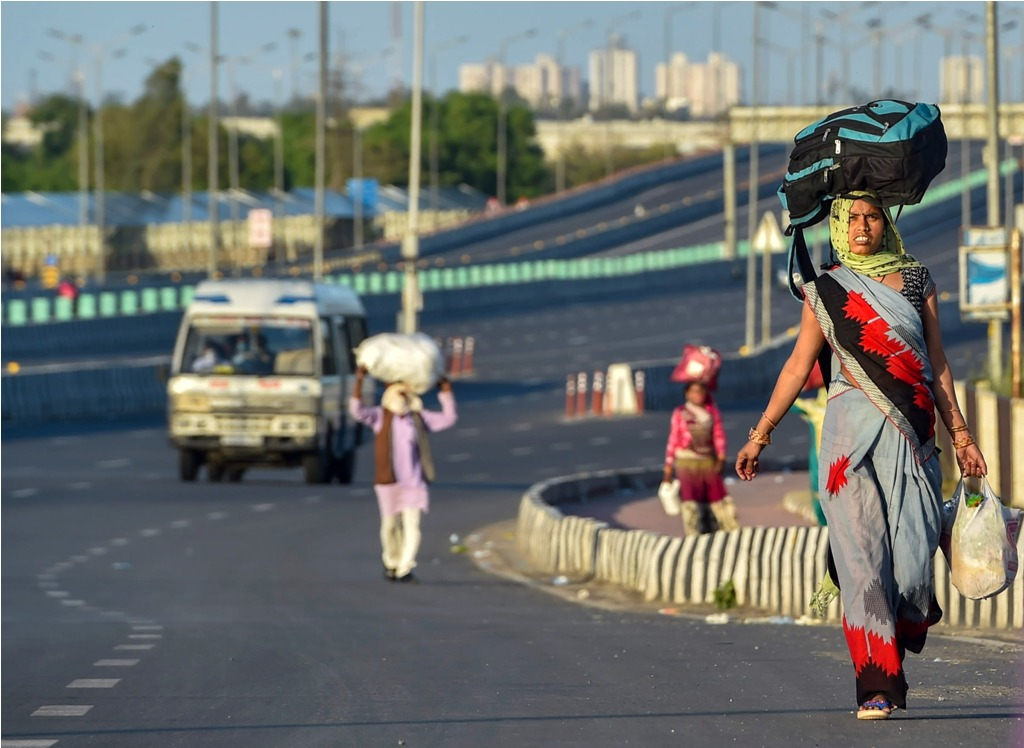 New Delhi: Migrant workers walk to their native village during a nationwide lockdown, imposed in the wake of coronavirus pandemic , at NH 24 near Akshardham in East Delhi, Sunday, March 29, 2020. (PTI Photo/Manvender Vashist)(PTI29-03-2020 000148B)
