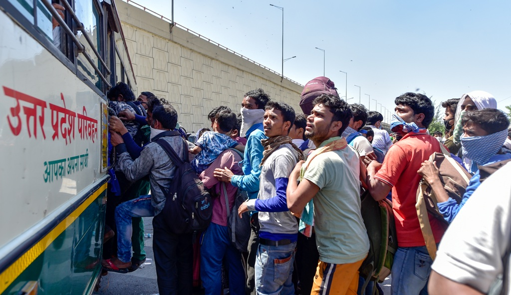 Ghaziabad: Migrants board a bus to their native village, during a nationwide lockdown imposed in the wake of coronavirus pandemic, at Ghazipur Delhi - UP border, Ghaziabad, Saturday, March 28, 2020. (PTI Photo/Vijay Verma) (PTI28-03-2020 000071B)