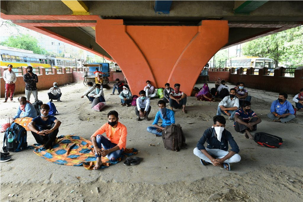 Ghaziabad: Migrant labourers made to sit under a flyover on the Hapur Road at a safe social distance by the district administration, during complete lockdown in the view coronavirus pandemic, in Ghaziabad, Thursday, March 26, 2020. (PTI Photo/Arun Sharma)