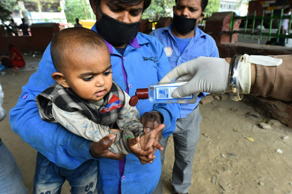 A policeman gives hand sanitiser to a child as a group of migrant labourers are made to stay under a flyover on the Hapur Road by the administration for their safety, in Ghaziabad. Photograph: Arun Sharma/PTI Photo