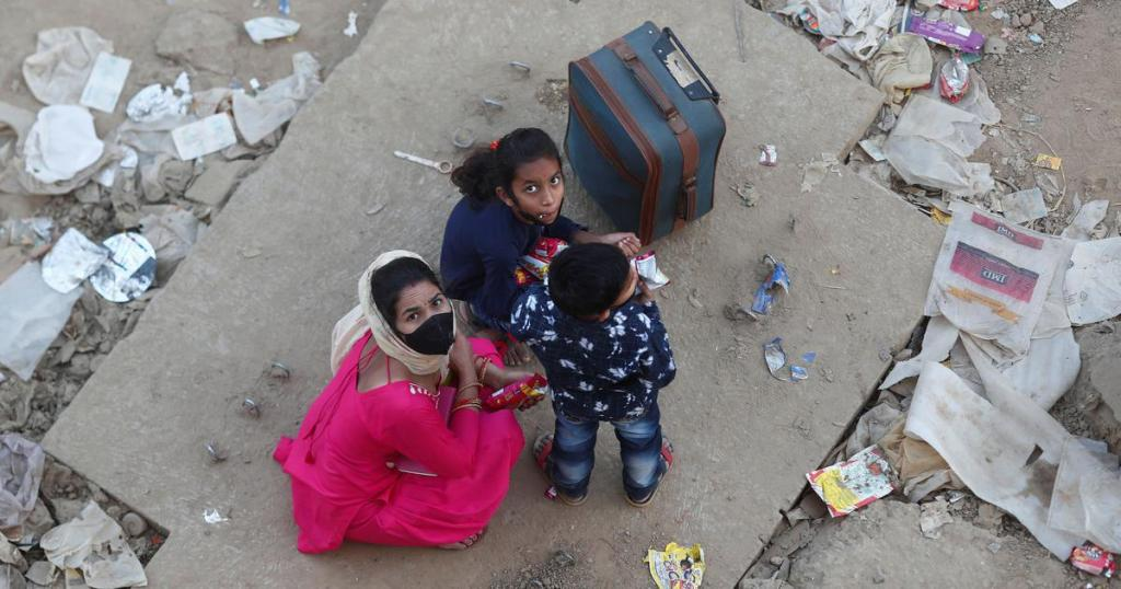 A migrant worker's family in Ghaziabad sits along a highway after they failed to get a bus to return to their village. | Adnan Abidi/Reuters
