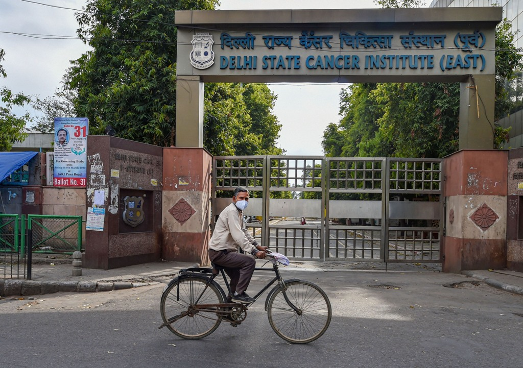 New Delhi: A cyclist wearing a mask rides past the Delhi State Cancer Institute (DSCI)during the nationwide lockdown, imposed as a preventive measure against the coronavirus pandemic, in East Delhi, Monday, April 20, 2020. (PTI Photo/Manvender Vashist) (PTI20-04-2020_000281B)