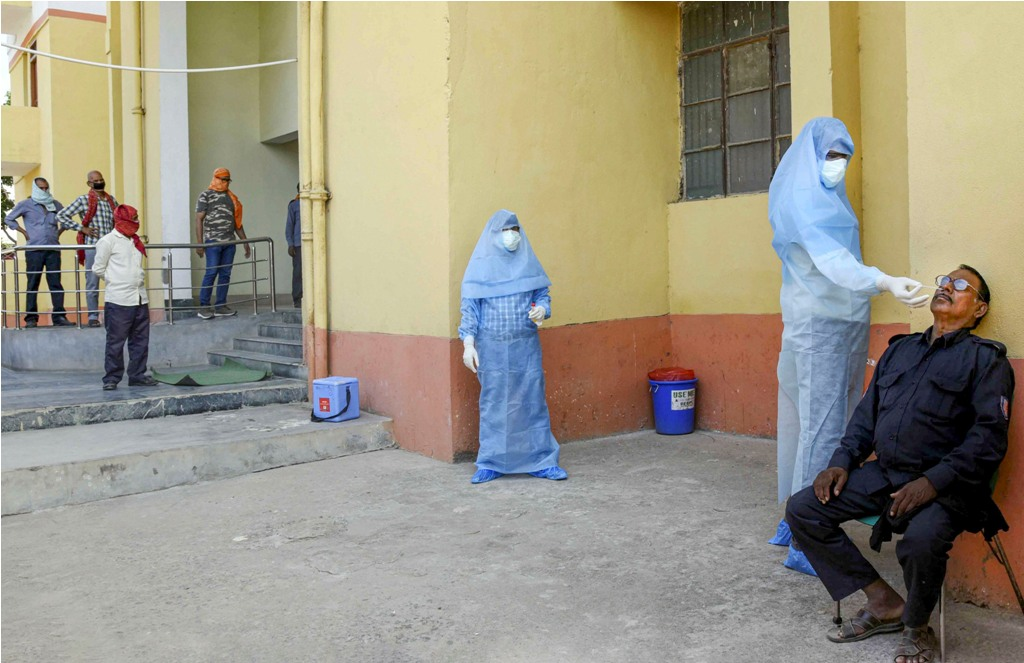 Patna: A medic wearing a protective suit takes a swab sample of a security guard during a nationwide lockdown in the wake of coronavirus pandemic, in Patna, Wednesday, April 22, 2020. (PTI Photo)(PTI22-04-2020_000110B)