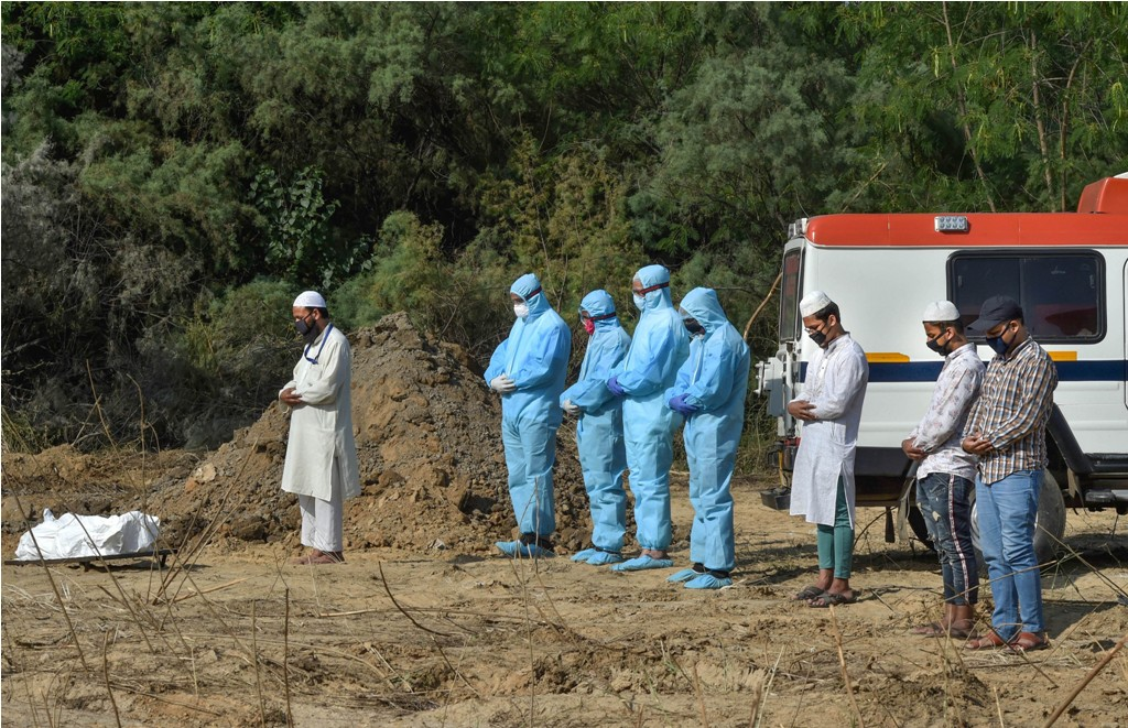 New Delhi: Medics and family members perform burial of a person who died of COVID-19, during the nationwide lockdown, in New Delhi, Wednesday, April 22, 2020. (PTI Photo/Manvender Vashist) (PTI22-04-2020_000200B)