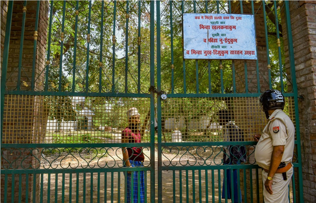 Prayagraj: A policeman stands guard outside a graveyard to stop the Shab-e-Barat gatherings of Muslims, during the nationwide lockdown imposed in the wake of coronavirus pandemic, in Prayagraj, Thursday, April 9, 2020. (PTI Photo) (PTI09-04-2020_000107B)