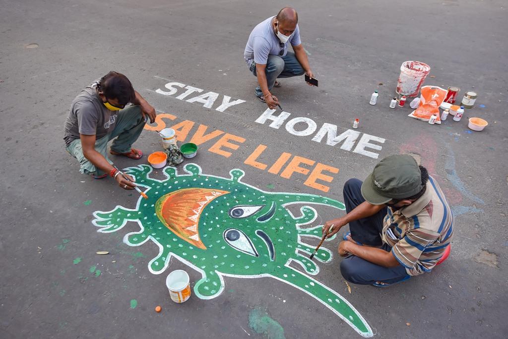 Kolkata: Artists paint graffiti on a road to raise awareness about the COVID-19 during nationwide lockdown imposed to contain the coronavirus pandemic, in Kolkata, Thursday, April 9, 2020. (PTI Photo/Swapan Mahapatra) (PTI09-04-2020_000142B)