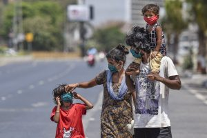 Mumbai: A family wearing face masks walk along a road during the nationwide lockdown, imposed in the wake of the coronavirus pandemic, at Worli in Mumbai, Thursday, April 9, 2020. (PTI Photo/Kunal Patil)(PTI09-04-2020_000174B)