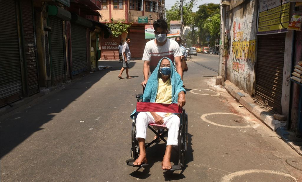 Kolkata: A man helps a physically challenged person during the nationwide lockdown to curb the spread of coronavirus, in Kolkata, Friday, April 10, 2020. (PTI Photo/Ashok Bhaumik)(PTI10-04-2020 000079B)