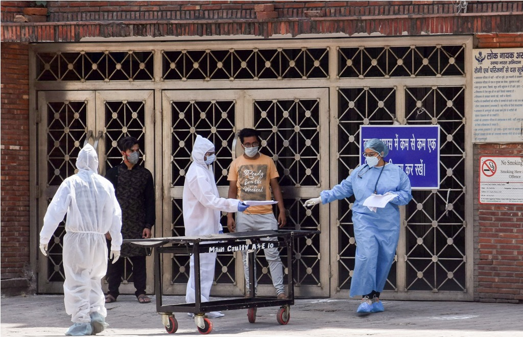 New Delhi: Medics wearing protective suits are seen outside the building gate of Lok Nayak Jai Prakash Narayan (LNJP) hospital during  the nationwide lockdown to curb the spread of coronavirus, in New Delhi, Friday, April 10, 2020. The hospital will function as a dedicated Covid-19 treating facility. (PTI Photo) (PTI10-04-2020_000105B)