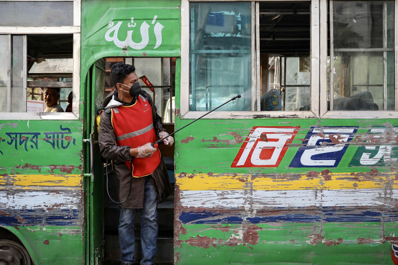 A volunteer sprays disinfectant inside a bus amid concerns about the spread of coronavirus disease (COVID-19) in Dhaka, Bangladesh, March 18, 2020. REUTERS/Mohammad Ponir Hossain