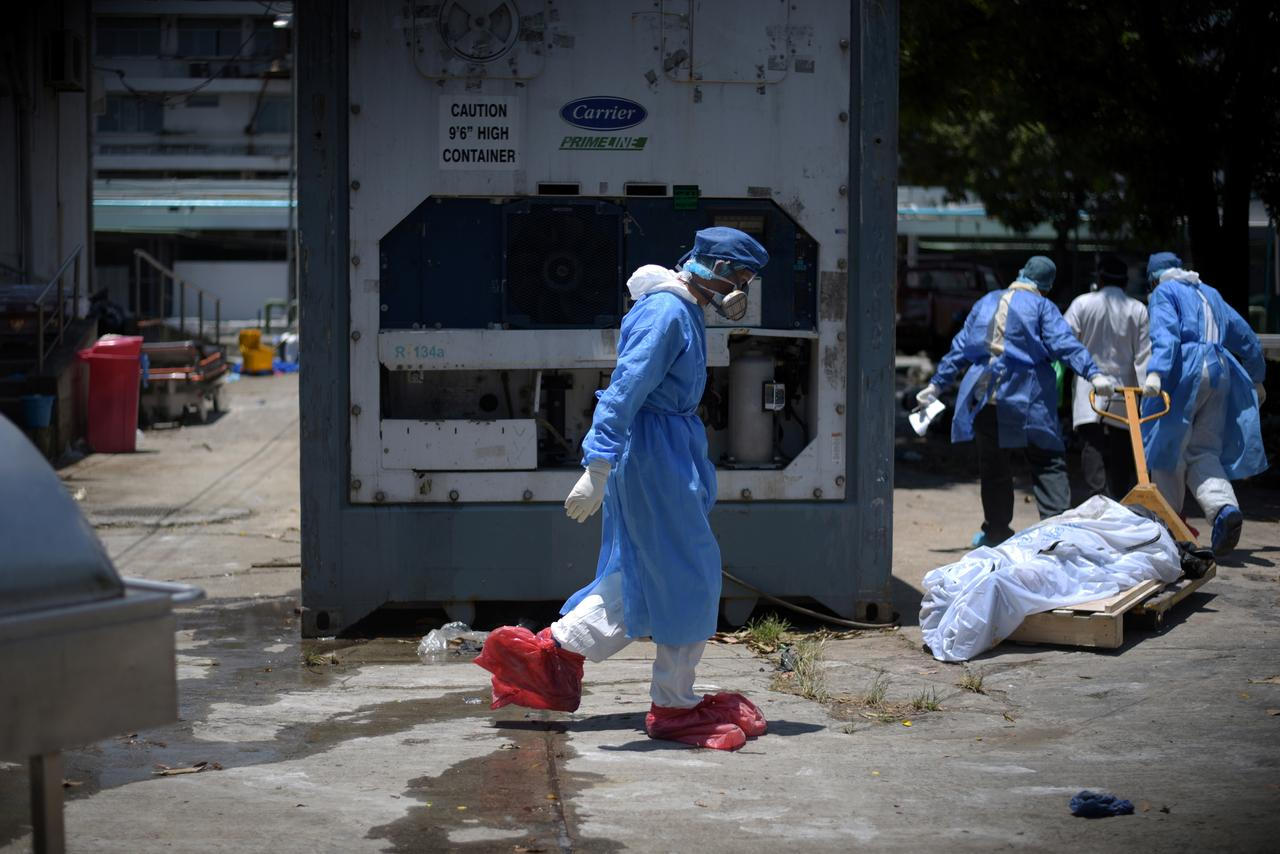 Health workers wearing protective gear bring a dead body past a refrigerated container outside of Teodoro Maldonado Carbo Hospital amid the spread of the coronavirus disease (COVID-19), in Guayaquil, Ecuador April 3, 2020. Picture taken April 3, 2020. REUTERS/Vicente Gaibor del Pino