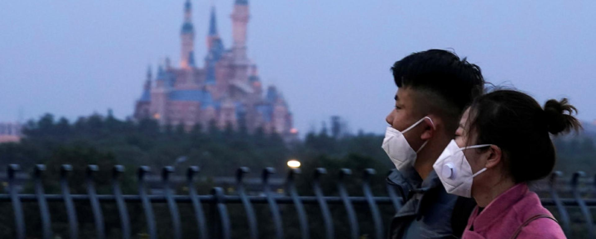 Visitors wearing masks walk past Shanghai Disney Resort, China, on Friday. The resort was closed during the Chinese Lunar New Year holiday on Saturday following the outbreak of a new coronavirus. Reuters