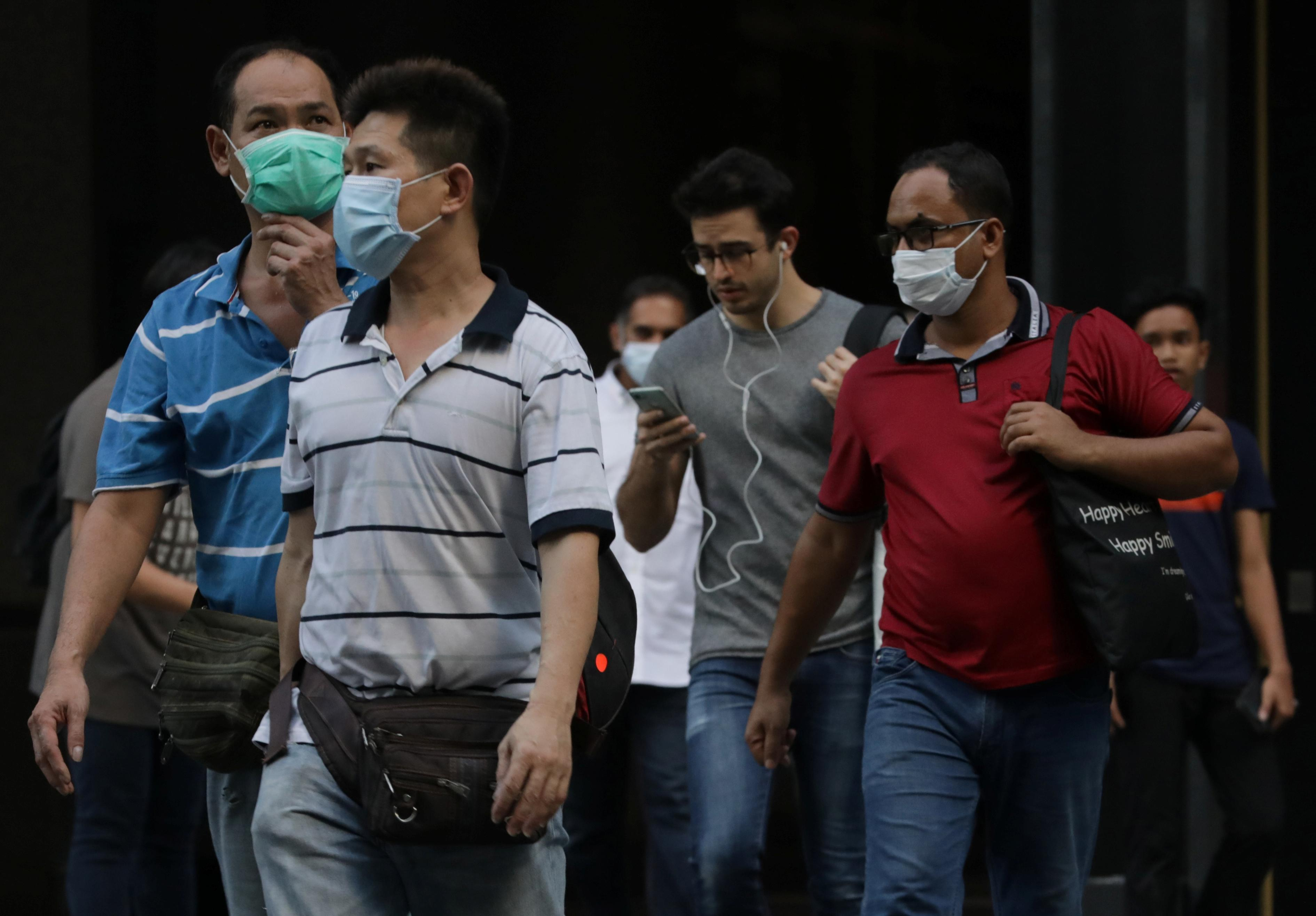 People wearing masks cross a street, during the outbreak of coronavirus disease (COVID-19), in Singapore's central business district. (Reuters photo)