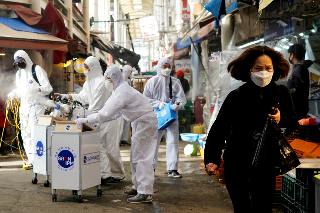 A woman who wears a mask to avoid contracting the coronavirus reacts when employees of a disinfection service company disinfect a traditional market in Seoul, South Korea. February 26, 2020. (REUTERS / Kim Hong-Ji)