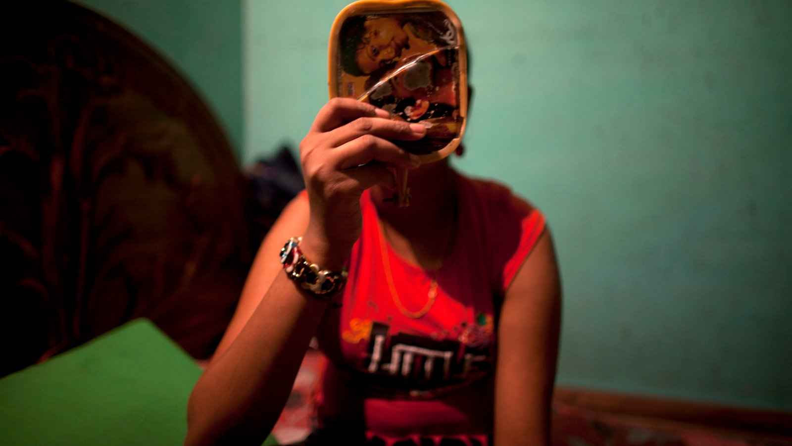 Twelve-year-old prostitute Mukti applies makeup before serving a customer inside her small room at a brothel in Faridpur, located in central Bangladesh February 22, 2012. REUTERS/Andrew Biraj