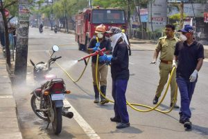 SDRF and Fire brigade officials spray disinfectant on a bike in the wake of the coronavirus, in Nagaon. PTI Photo