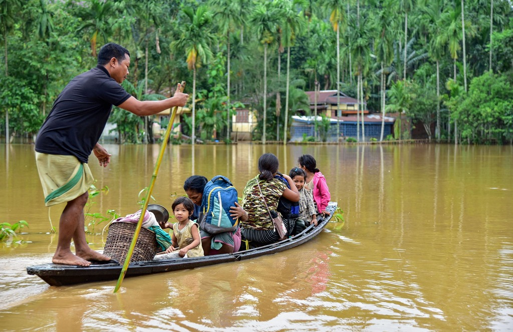 Goalpara: Villagers use a country boat to shift from a flooded locality following heavy rainfall at Bolbola in Goalapra district of Assam, Monday, May 25, 2020. Heavy rainfall caused flooding in hundreds of villages in Lower Assam. (PTI Photo) (PTI25-05-2020_000292B)