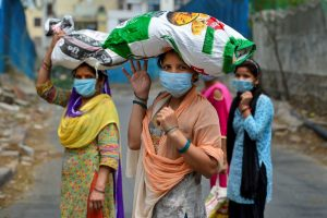 New Delhi: Women carry free ration collected from a fair price shop during the ongoing COVID-19 nationwide lockdown, in East Delhi,  Wednesday, May 6, 2020. (PTI Photo/Kamal Kishore)(PTI06-05-2020_000169B)