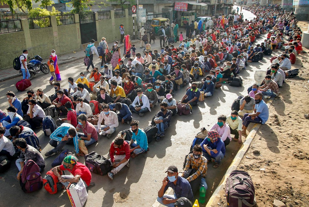 Ahmedabad: Migrants wait for a means of transport to reach a railway station and board a special train to their native place in Uttar Pradesh, during the ongoing COVID-19 nationwide lockdown, in Ahmedabad, Thursday, May 14, 2020. (PTI Photo)(PTI14-05-2020_000126B)