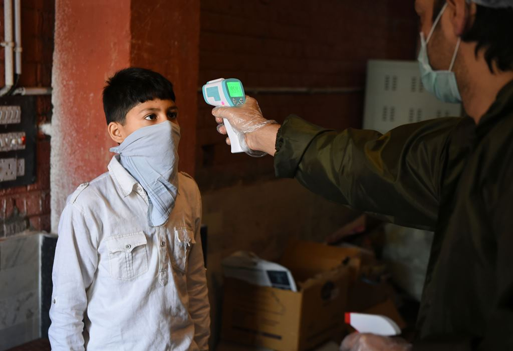 Srinagar: A man checks the temperature of a boy who came to buy sweets at a bakery shop ahead of Eid-ul-Fitr, during ongoing COVID-19 lockdown, in Srinagar, Wednesday, May 20, 2020. (PTI Photo/S. Irfan) (PTI20-05-2020 000153B)
