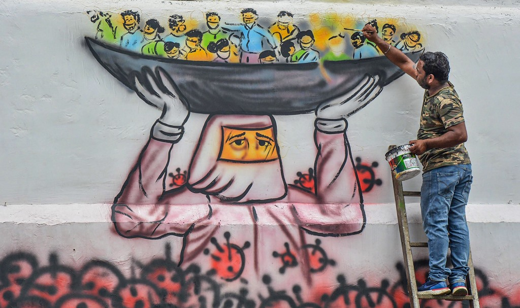 Guwahati: An artist paints a mural on a wall depicting a doctor saving people's lives from deadly coronavirus, during the ongoing nationwide lockdown, in Guwahati, Tuesday, May 19, 2020. (PTI Photo)(PTI19-05-2020_000202B)