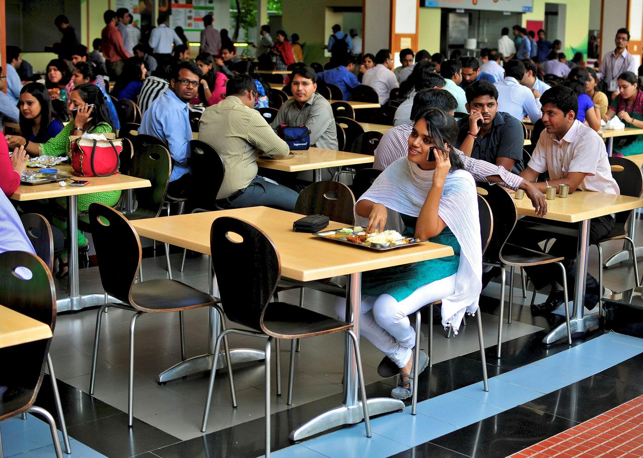 An employee speaks on a mobile phone as she eats her lunch at the cafeteria in the Infosys campus in Bengaluru, India, September 23, 2014. REUTERS/Abhishek N. Chinnappa/File Photo