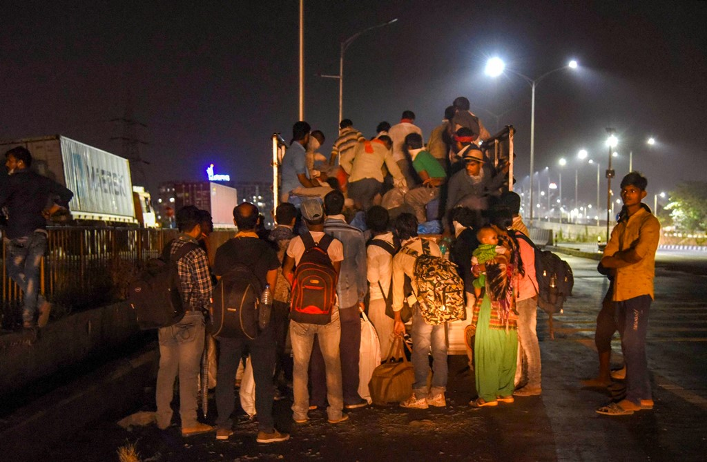 Navi Mumbai: Migrants from Uttar Pradesh and Bihar board a truck to reach their native places, during a nationwide lockdown in the wake of coronavirus pandemic, in Navi Mumbai, Tuesday, May 12, 2020. (PTI Photo)(PTI13-05-2020_000015B)