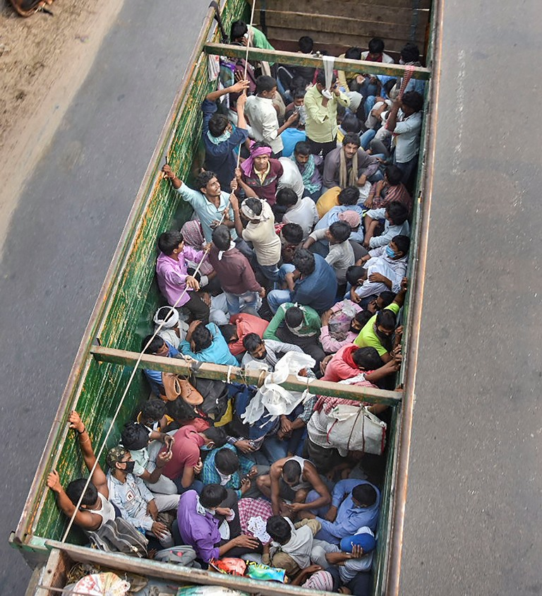 Mathura: Migrants ride a truck to reach their native places, during the ongoing COVID-19 lockdown, in Mathura, Wednesday, May 13, 2020. (PTI Photo)(PTI13-05-2020 000028B)