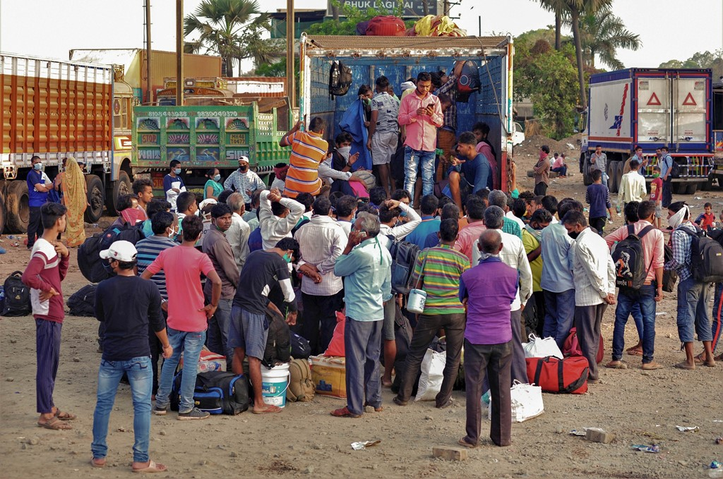 Mumbai: Migrants board a truck to travel to their native places in UP during the ongoing COVID-19 nationwide lockdown, in Mumbai, Wednesday, May 13, 2020. (PTI Photo) (PTI13-05-2020_000066B)