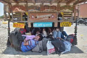 Thane: Migrants from northern states take rest under a truck on the Mumbai-Nashik highway enroute their journey to their native places, amid ongoing COVID-19 lockdown in Thane, Monday, May 11, 2020. (PTI Photo/Mitesh Bhuvad) (PTI11-05-2020_000139B)